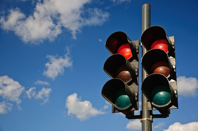 A couple of red traffic lights against a blue sky by Horia Varlan